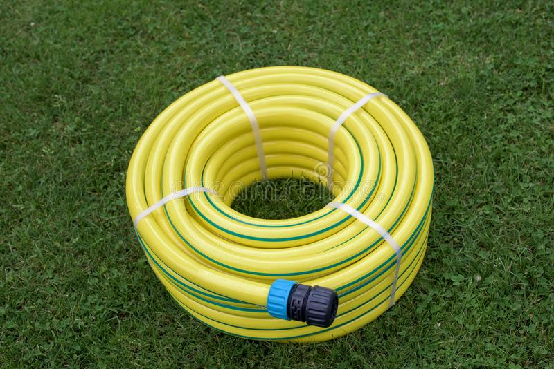 New yellow hose pipe in a garden stock images