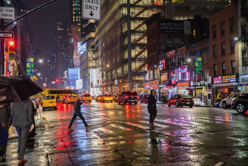 New York Broadway gator på natten Upplysta höga byggnader, färgrika neonljus, annonser och gå för folk arkivfoto