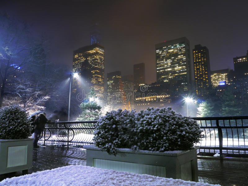 New York - Central Park Skate Rink In Christmas Snow. A festive Ice Skating rink is watched by onlookers reveling in the magical atmosphere in Manhattan in royalty free stock photo