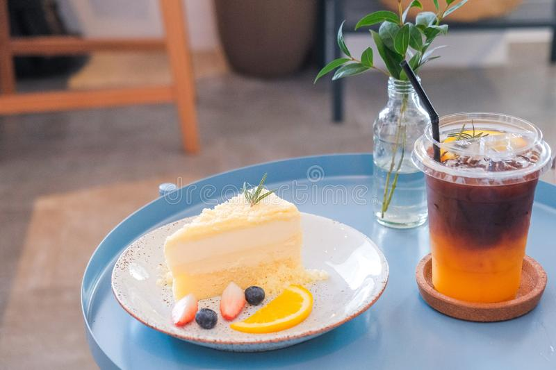 New York cheesecake or classic cheesecake with fresh fruits and ice coffee on white plate. In cafe background stock image