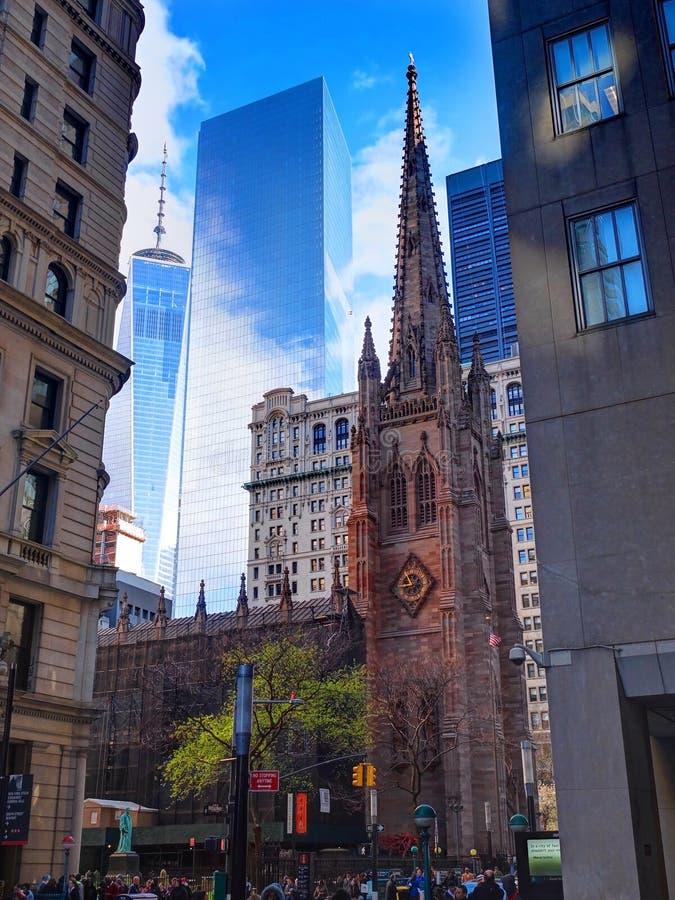 NEW YORK CITY, ABRIL, 24, 2015: Opinião da rua de Broadway na igreja de trindade dos prédios de escritórios, arranha-céus próximo foto de stock royalty free