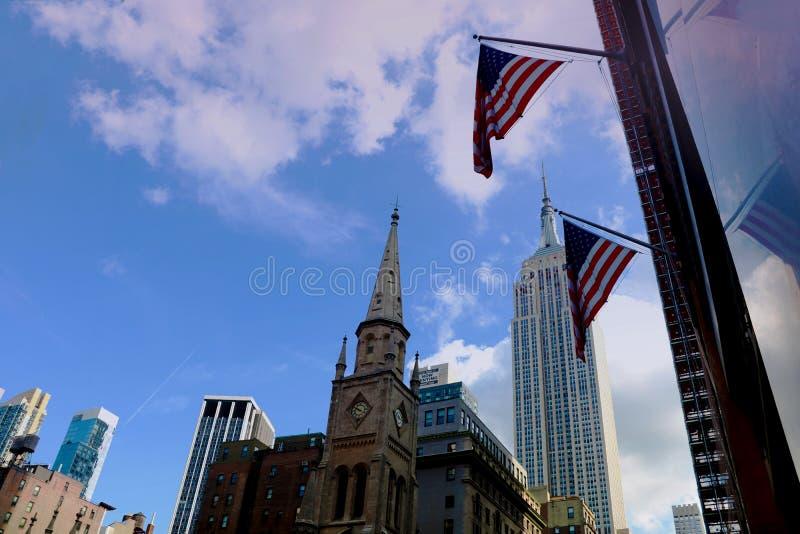 New York City - 25. August 2018: Empire State Building und US-Flaggen stockfotografie
