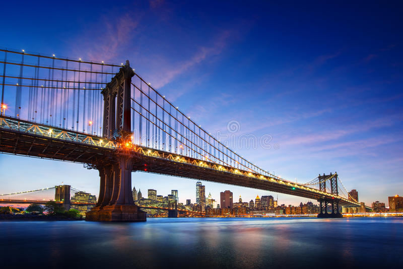 New York City - beautiful sunset over manhattan with manhattan and brooklyn bridge stock image