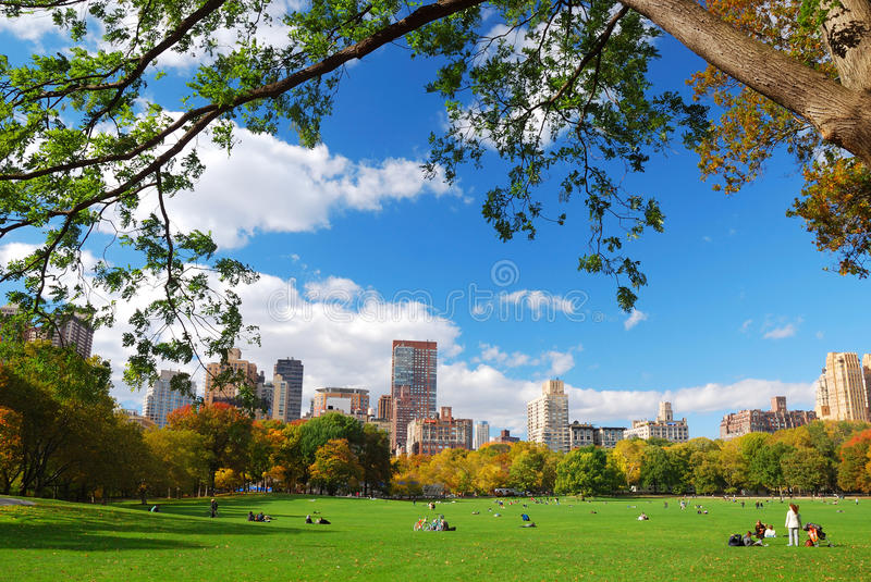 New York City Central Park with cloud and blue sky. New York City Manhattan skyline panorama viewed from Central Park with cloud and blue sky and people in lawn stock photo