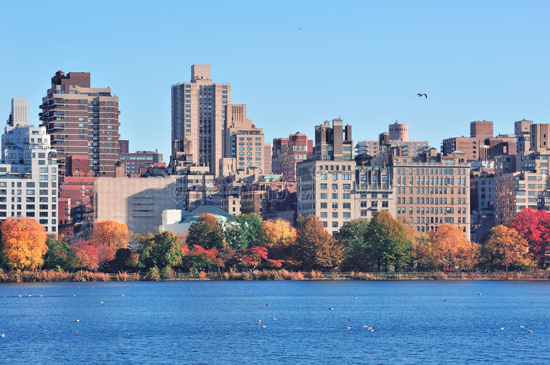 New York City Central Park over lake. Central Park Autumn with New York City Manhattan Midtown skyline skyscrapers over lake with colorful foliage and clear blue royalty free stock photos
