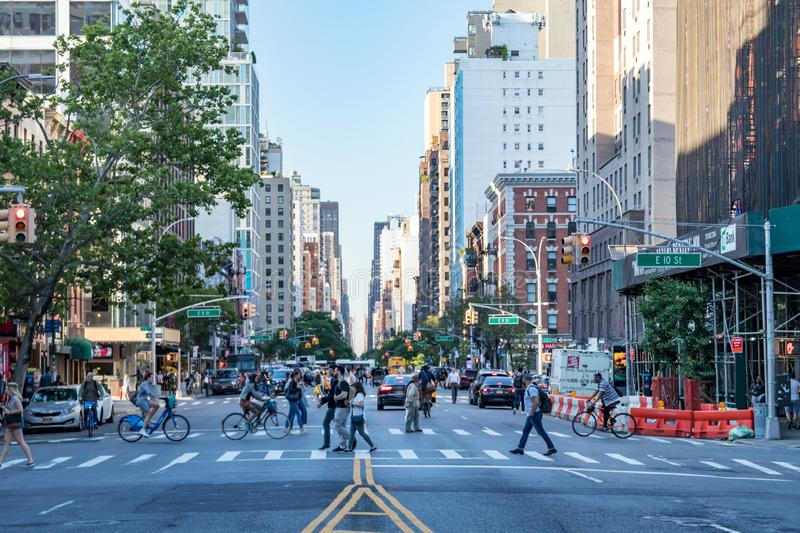 New York City, 2018: Crowds of people walk across the bus stock photography