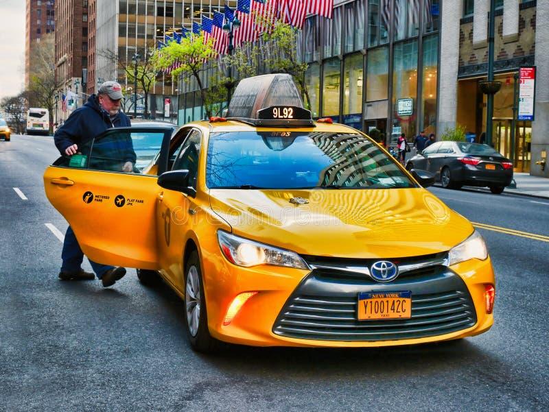 New York City, EUA - em abril de 2018: Homem que obtém no táxi amarelo em Manhattan imagem de stock royalty free