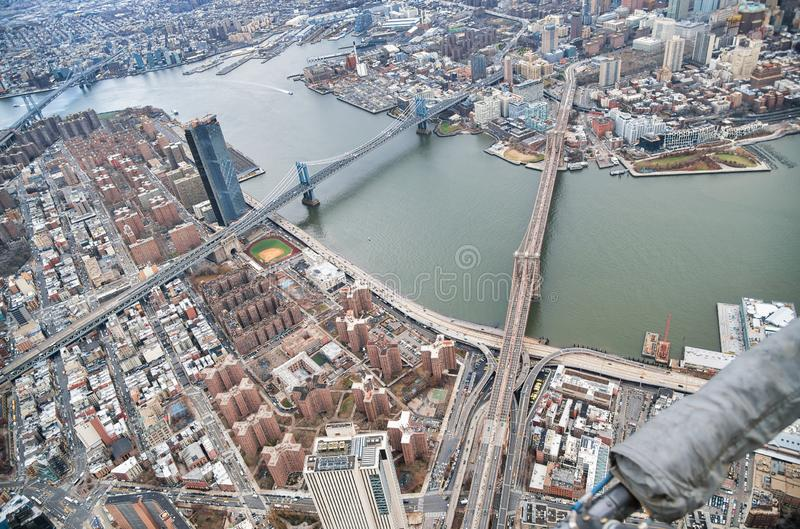New York City from helicopter point of view. Brooklyn, Manhattan and Williamsburg Bridges with Manhattan skyscrapers on a cloudy stock photos