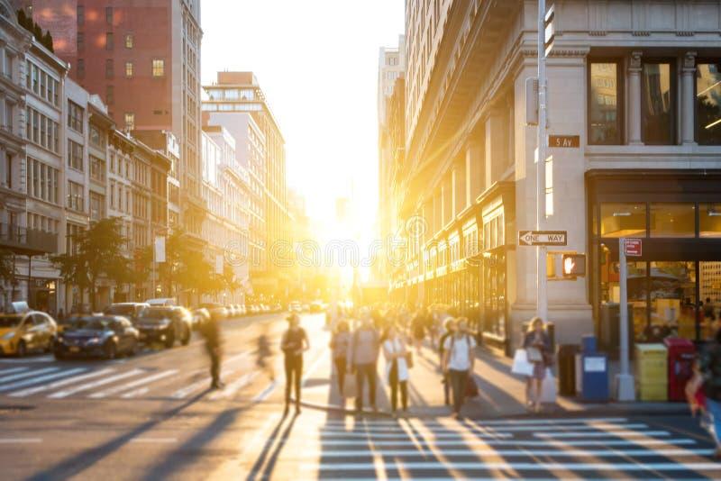 New York City - helles Licht des Sonnenuntergangglanzes auf Mengen von den Leuten, die den Schnitt auf 5. Allee in Manhattan kreu lizenzfreies stockbild