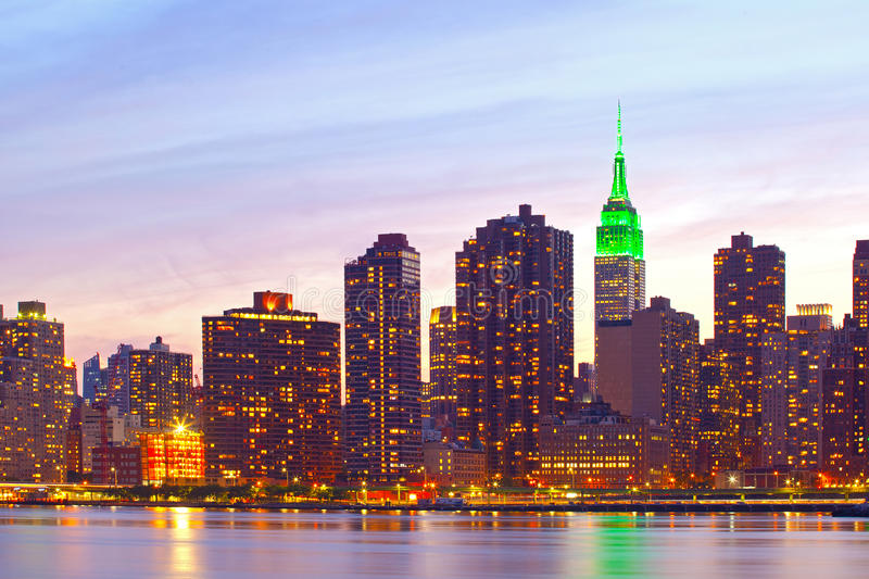 New York City, Manhattan famous landmark buildings. Skyline in downtown at beautiful colorful sunset with reflections stock image