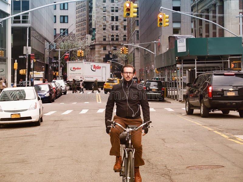 NEW YORK CITY, MANHATTAN, OUTUBRO, 25, 2013: Vista no homem inteligente na equitação da bicicleta na estrada da rua de NYC entre  foto de stock