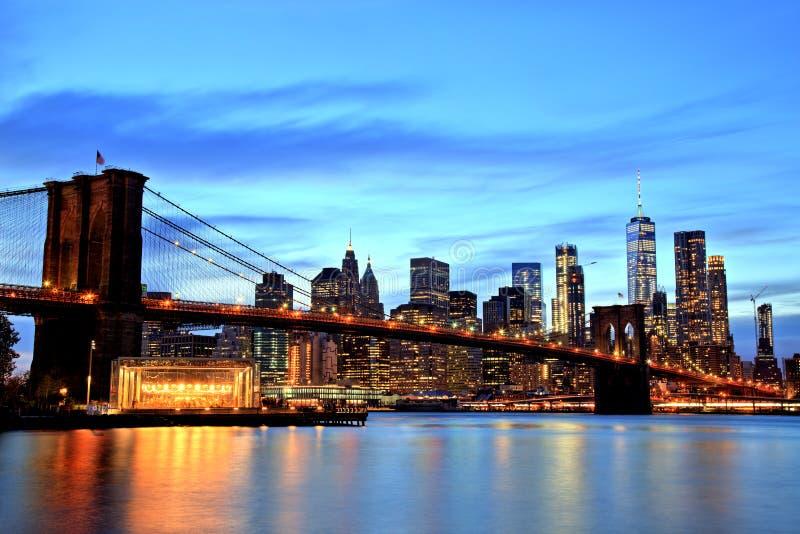 New York City Manhattan som är i stadens centrum med den Brooklyn bron på skymning arkivfoto