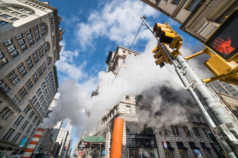 New York City Manhattan street in Midtown with steam, signs and signals at sunny day. stock images