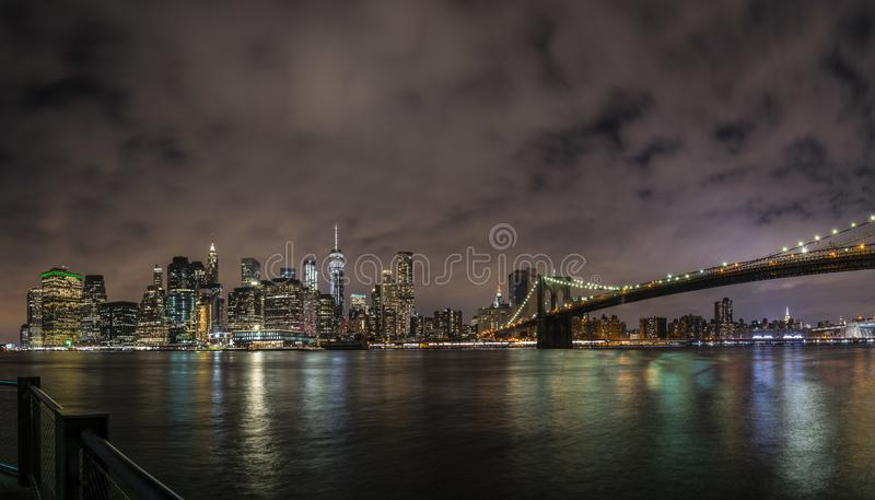 New York City Manhattan downtown panorama at night with skyscrapers illuminated over east river stock photo