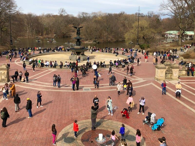 New York City New York - mars 24, 2019: Folk som tycker om en solig och varm dag på Bethesda Fountain i Central Park, New York royaltyfria foton