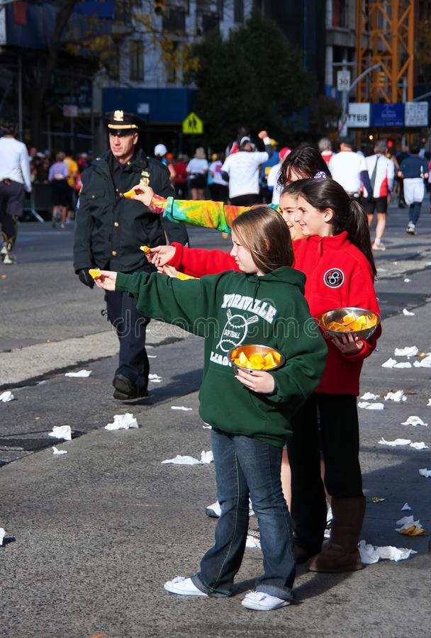 Young Girls Handing Snacks to Marathon Runners. New York City, NY USA. Nov 2008. Young girls handing out oranges to runners by a patrolling police officer during royalty free stock photo