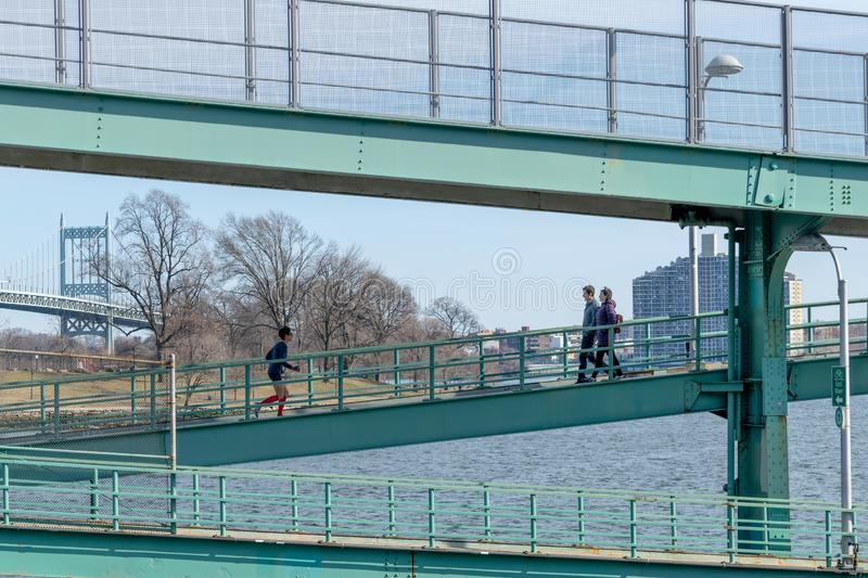 New York City, NY/USA - 3/19/2019: People walking an jogging along a steel structure next to the East River, with the. New York City, NY/USA - 3/19/2019: People royalty free stock photo