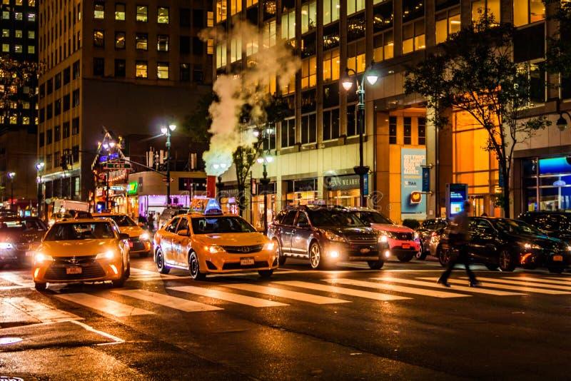 New York City, Ost46. Straße, Manhattan - 1. November 2017: Rauch läuft aus Kanaldeckel hinter Linie von gelben Fahrerhäusern her lizenzfreies stockfoto