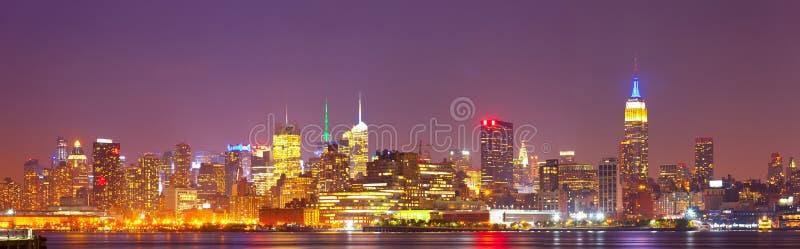 New York City panorama för USA färgrik natthorisont arkivbilder