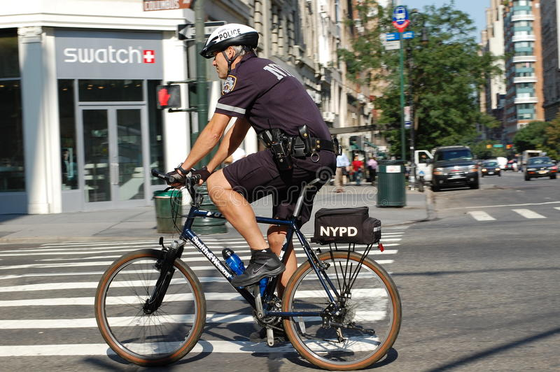 New York City Police Bike Squad. A policeman on bicycle pedals down Columbus Avenue. Bicycles can navigate places in the city that are not accessible to squad royalty free stock photo