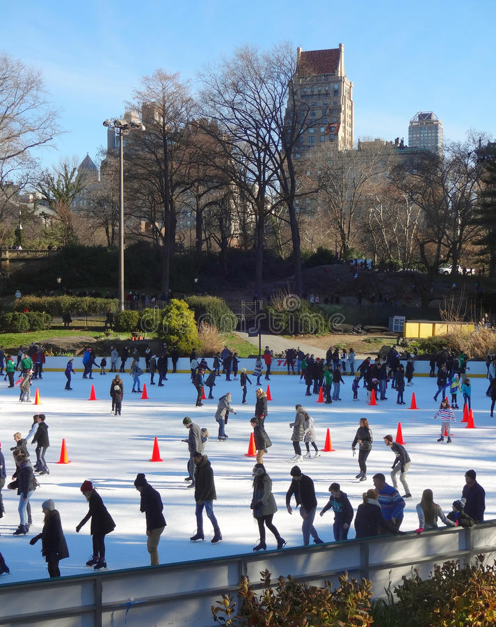 New York City's Central Park Skating Rink. Skaters enjoying the rink inside New York City's Central Park on a clear day with the skyline in the background stock photo