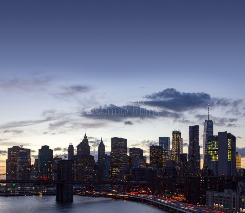 New York City skyline lights at dusk with the Brooklyn Bridge royalty free stock photos