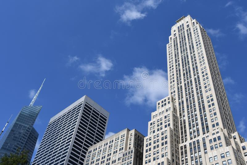 New York City skyscraper in Midtown Manhattan. On a sunny day with trees and a blue sky stock image