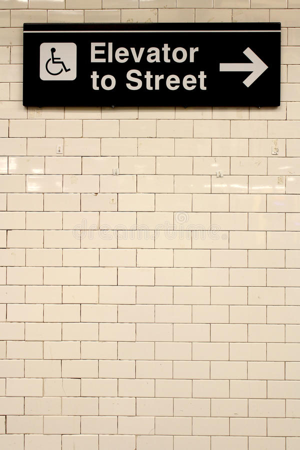 New York City Station subway directional sign on tile wall. The NYC Subway is one of the oldest and most extensive public transportation systems in the world royalty free stock photography