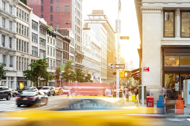 New York City street scene with yellow taxi cab driving down 5th Avenue through Midtown Manhattan. NYC royalty free stock images