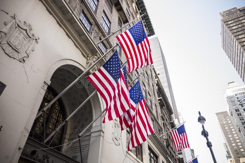New York City, United States. Multiple American flags waving from the facade of a building stock photo