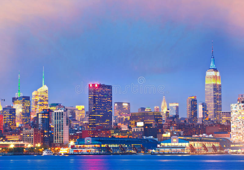 New York City, USA. Downtown buildings in Manhattan. With colorful lights, panorama at sunset royalty free stock photos