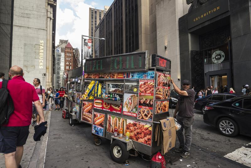 Vendor in its food truck in New York City, USA. New York City, USA - July 26, 2018: Vendor in its food truck with people around in Manhattan in New York City stock images