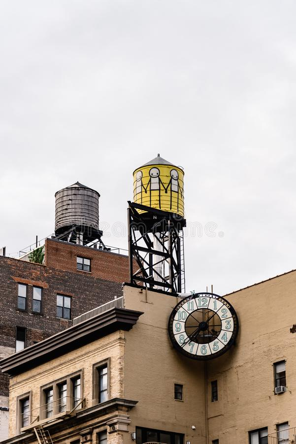 Low angle view of water towers and clock against sky in New York. New York City, USA - June 20, 2018: Low angle view of water towers and clock on top of old royalty free stock photos
