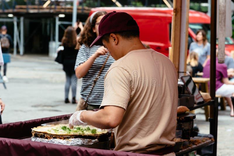 Brooklyn Flea Market in DUMBO in New York. New York City, USA - June 24, 2018: Man preparing fresh food in Brooklyn Flea Market in DUMBO. It includes vendors of royalty free stock photos