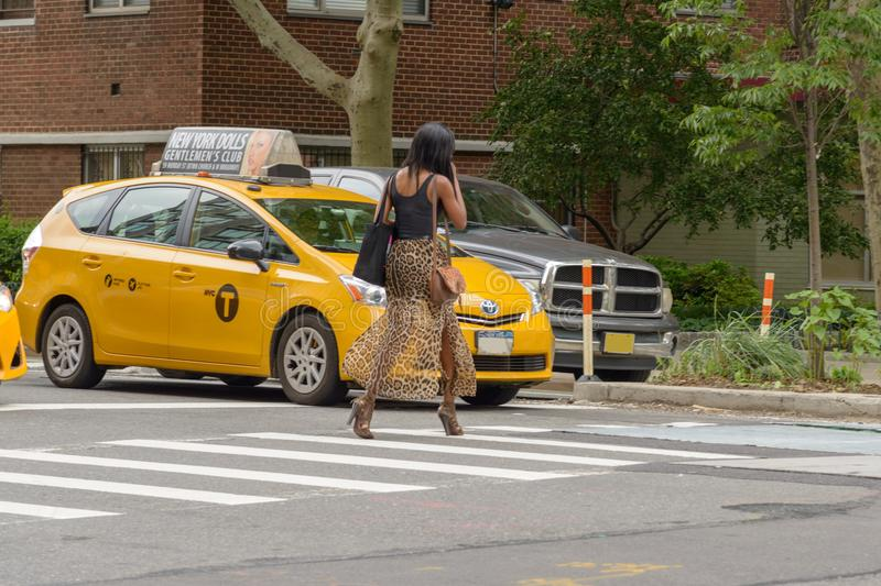 The American woman crosses the pedestrian crossing while the tax royalty free stock image