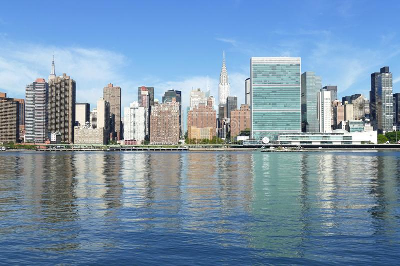 New York City Waterfront, East River and Manhattan Skyline with blue sky in the background royalty free stock photo