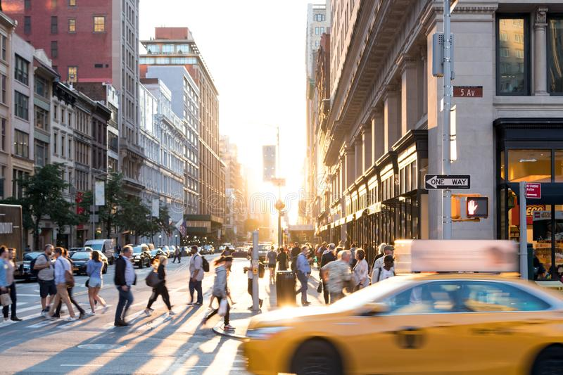 New York City yellow taxi cab speeds past the crowds of people in Midtown Manhattan stock images