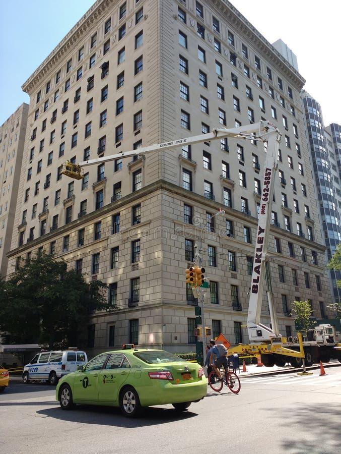 New York City, zona leste superior, 5a avenida, táxi verde, ciclista, polícia Van, guindaste, NYC, NY, EUA imagens de stock royalty free
