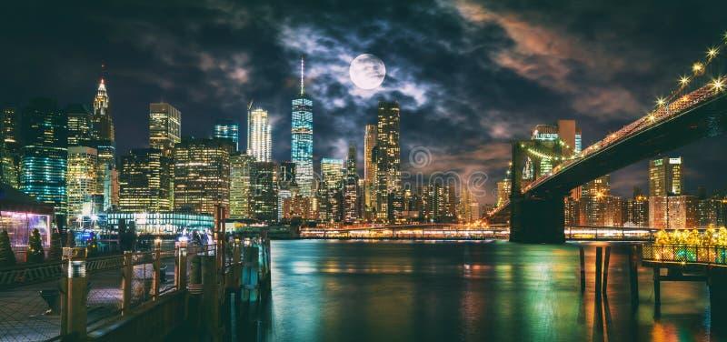 New- York Citybrooklyn-brücken- und Manhattan-Skyline belichtet nachts mit Vollmondunkosten stockfotos