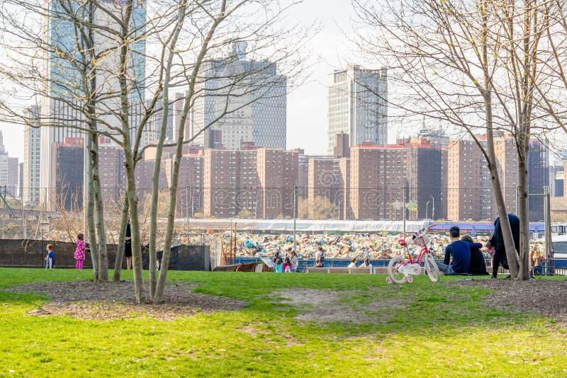 NEW YORK, DE V.S. - 28 APRIL, 2018: De mensen die bij de rivier van het Oosten van Brooklyn rusten overbruggen park in de Stad va stock foto's