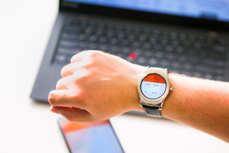 New York, de V.S. - 20 Augustus, 2015: Mens die de voorraadcitaten op zijn smartwatch kijken stock foto
