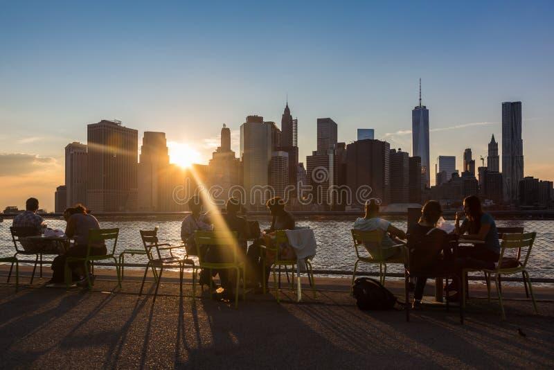 NEW YORK, DE V.S. - 25 AUGUSTUS, 2014: Mensen die bij zonsondergang in Br rusten stock foto