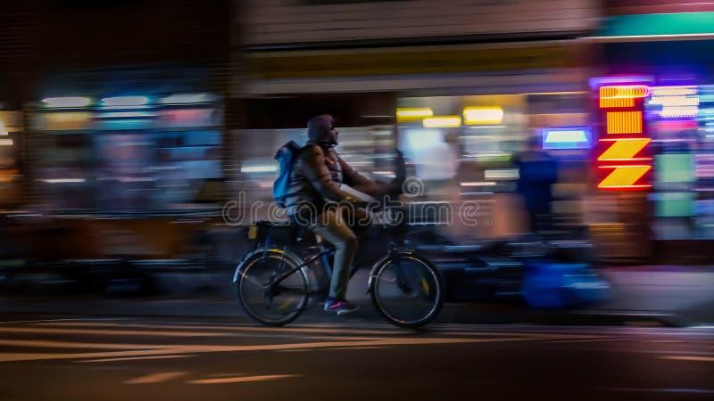 NEW YORK, DE V.S. - 18 MAART, 2018: Berijdende fietsers Bicyclistsin in stad, nacht, samenvatting Modern actief levensstijlconcep stock foto