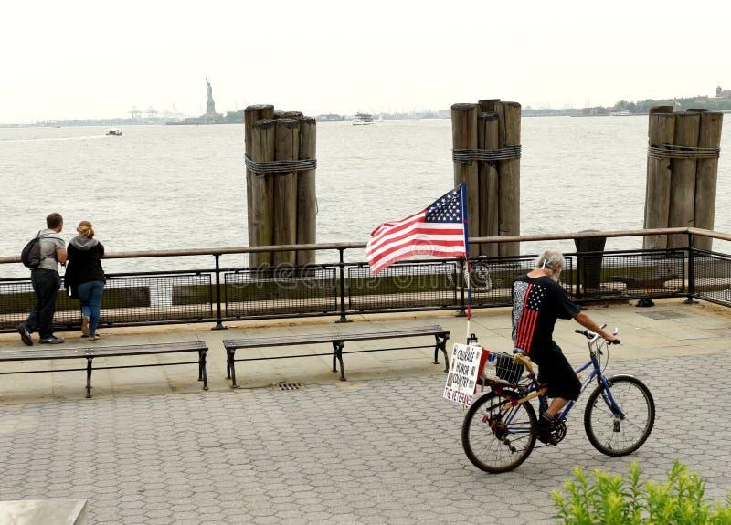New York, EUA - 28 de maio de 2018: Um homem com bandeira dos E.U. em uma bicicleta em B fotografia de stock royalty free