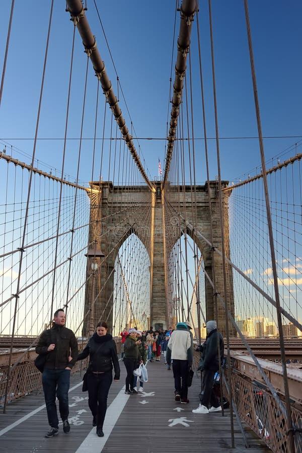 NEW YORK, EUA - 21 DE OUTUBRO DE 2018: Os pedestres andam sobre a ponte de Brooklyn no por do sol Ponte de Brooklyn de New York C imagens de stock royalty free