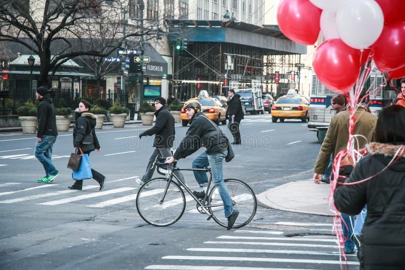 New York, EUA Fevereiro 2009 ciclista que cruza uma avenida de manhattan pela bicicleta fotografia de stock