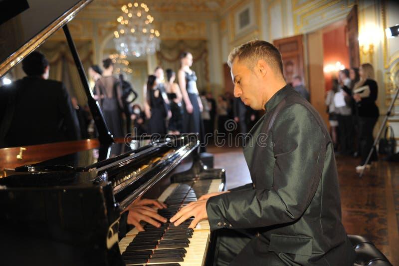 NEW YORK - FEBRUARI 06: De pianist presteert op piano en de modellen stellen bij statische presentatie voor de Russische Ontvangst stock afbeeldingen