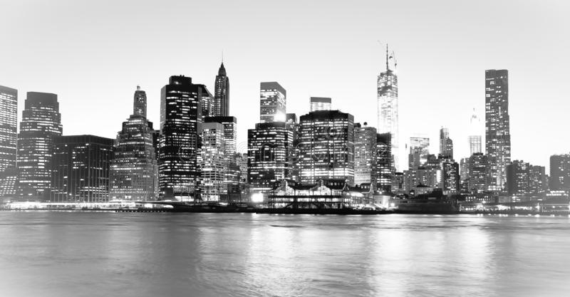 New York Financial District and the Lower Manhattan at night viewed from the Brooklyn Bridge Park. High key black and white image stock photography