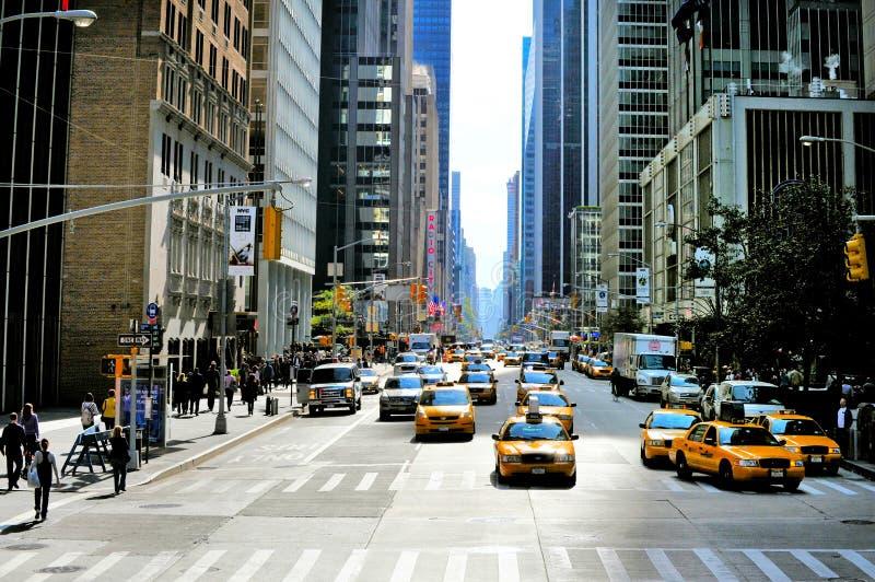 New York ingiallisce i taxi si precipita attraverso il sesto viale in Manhattan immagine stock