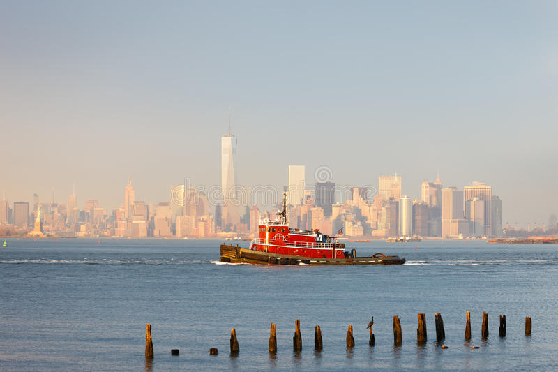 New York Lower Manhattan skyline with a tugboat. Tugboat in New York Harbor in afternoon soft winter light with the Financial District of Lower Manhattan in stock photo